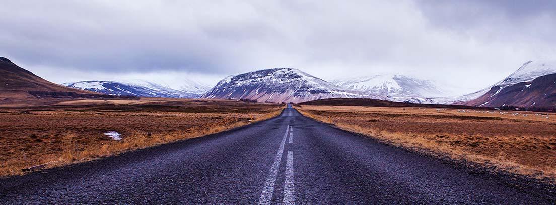 Vista panorámica de carretera abandonada con rayas blancas en medo y montaña al fondo.