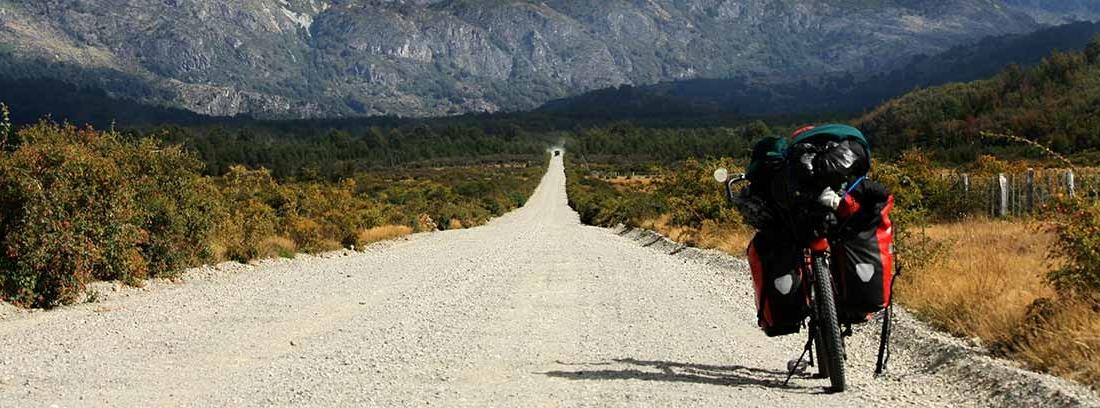 Moto aparcada en el lateral de una vieja carretera de montaña abandonada.