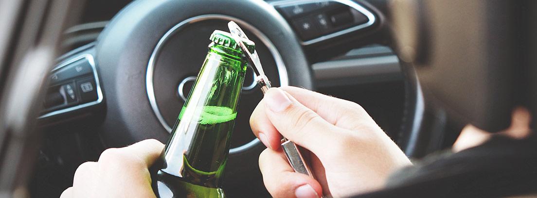 Hombre al volante abriendo un botellín de cerveza