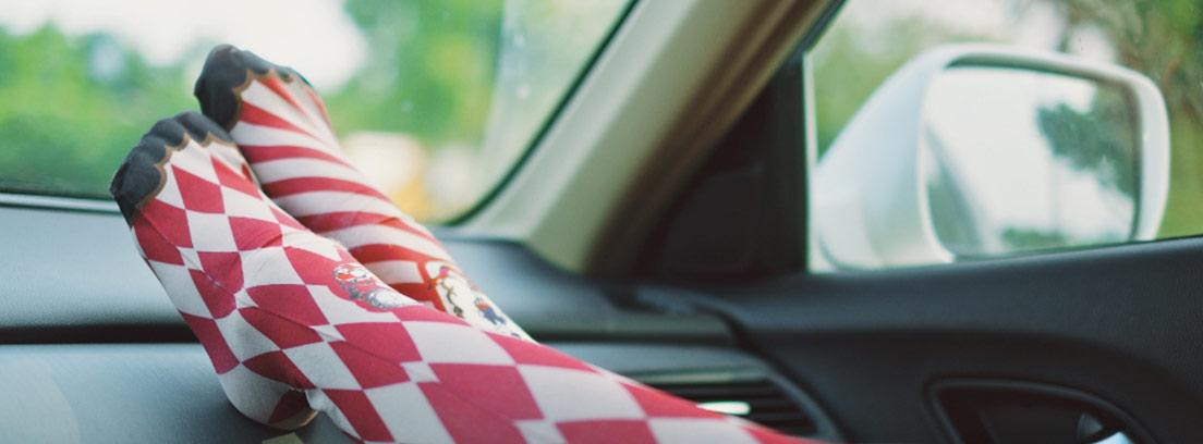Piernas con medias de rombos sobre el salpicadero de un coche