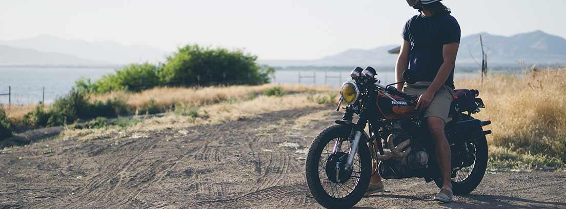 Hombre montado en moto con casco parado mirando hacia paisaje de mar.