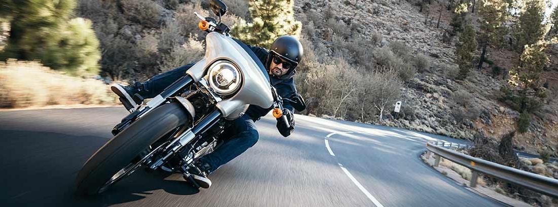 Hombre montado en moto tomando curva