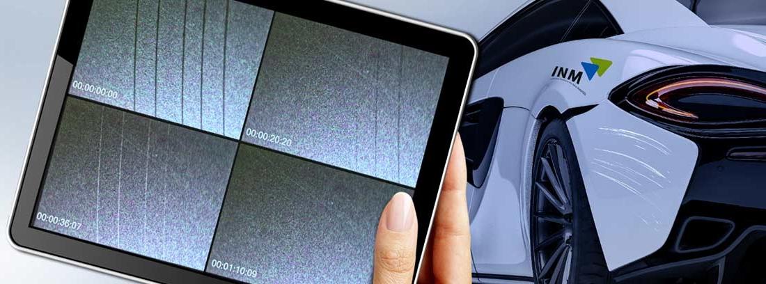 Mano con una tablet en la que se ve el proceso de la pintura de coche autorreparable y un coche al fondo