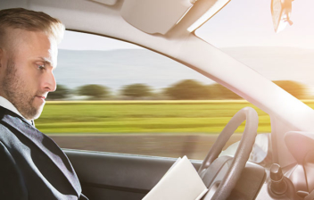 Hombre leyendo mientras su coche conduce solo