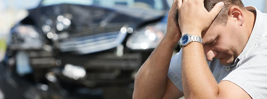 Mujer llevándose las manos a la cabeza frente a dos coches siniestrados