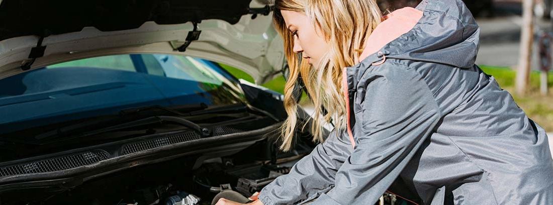 Mujer con manos dentro del motor de un coche