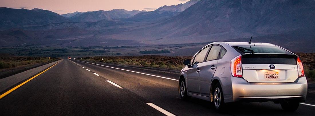 Coche circulando por carretera junto a montañas