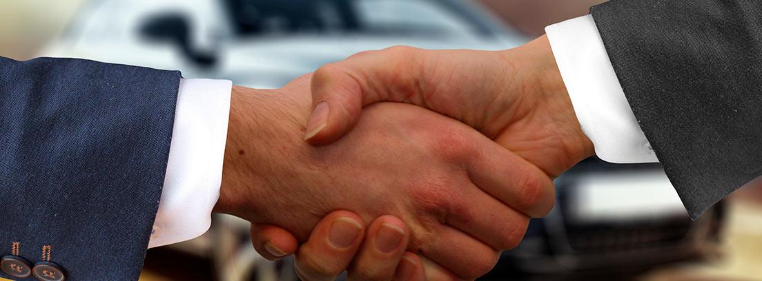 Apretón de manos en señal de acuerdo delante de un coche