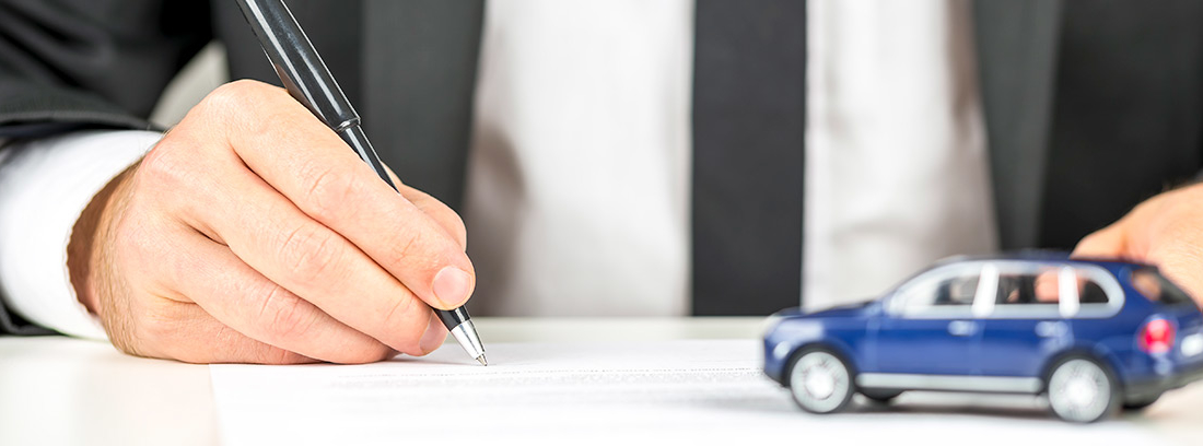Mano firmando un papel con un coche de juguete al lado