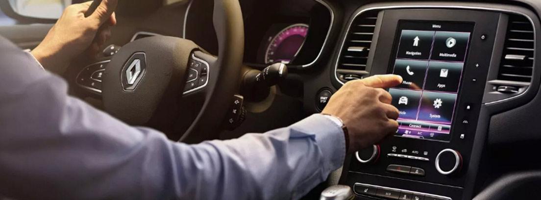 Interior de un coche Renault sobre el volante el logo en forma de diamante