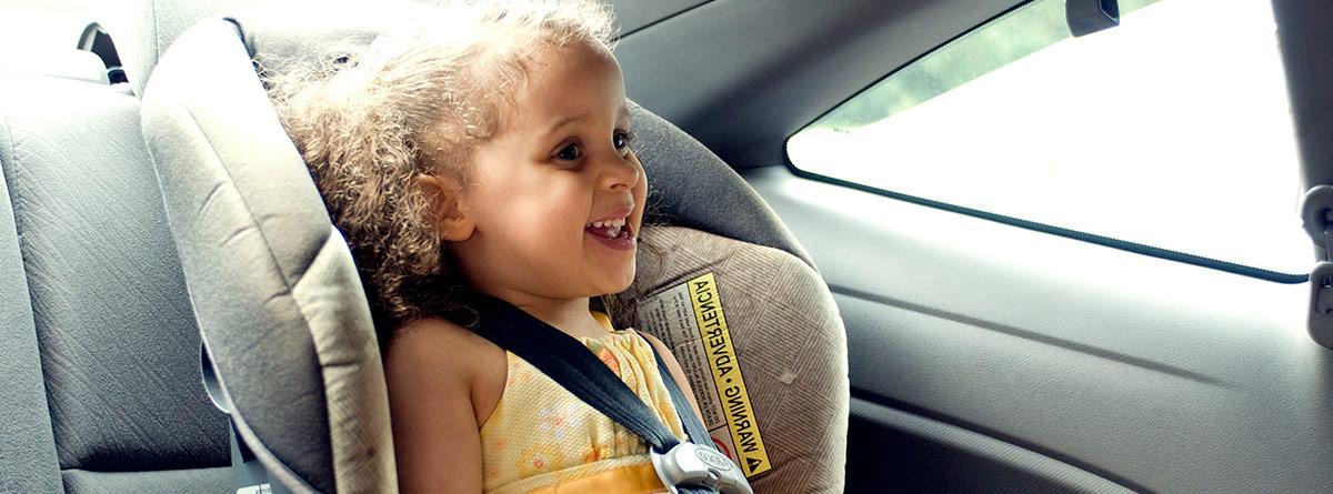 Niña sentada en un sistema de retención infantil