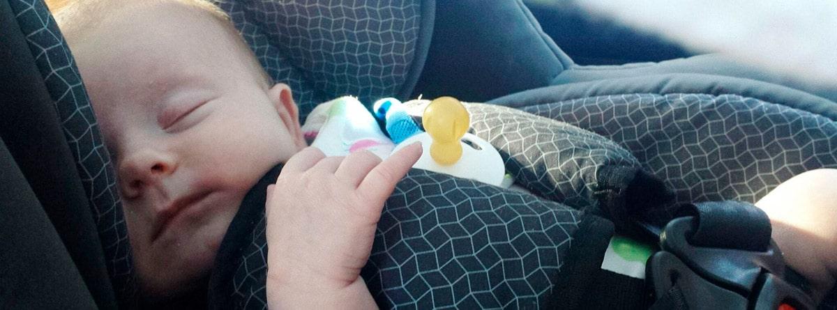 Bebé dormido en una silla para el coche
