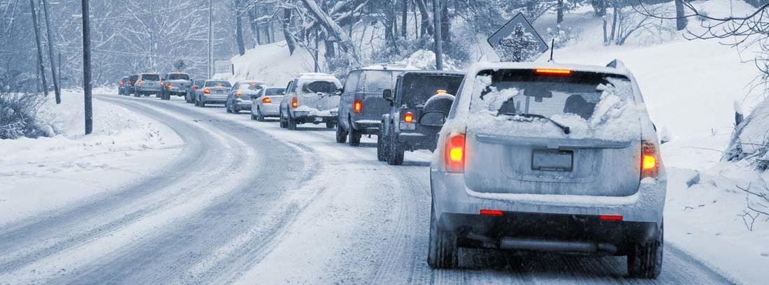 varios coches en fila circulando con nieve