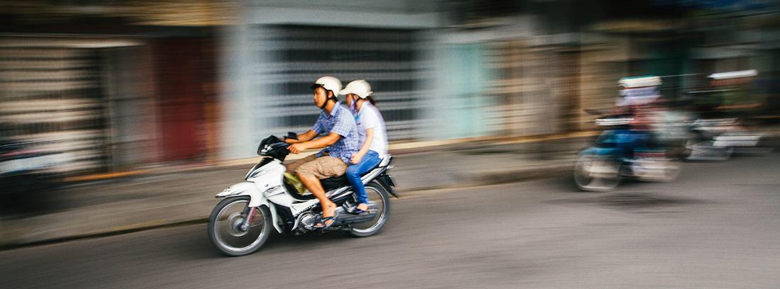Dos personas subidas en una moto circulando por ciudad