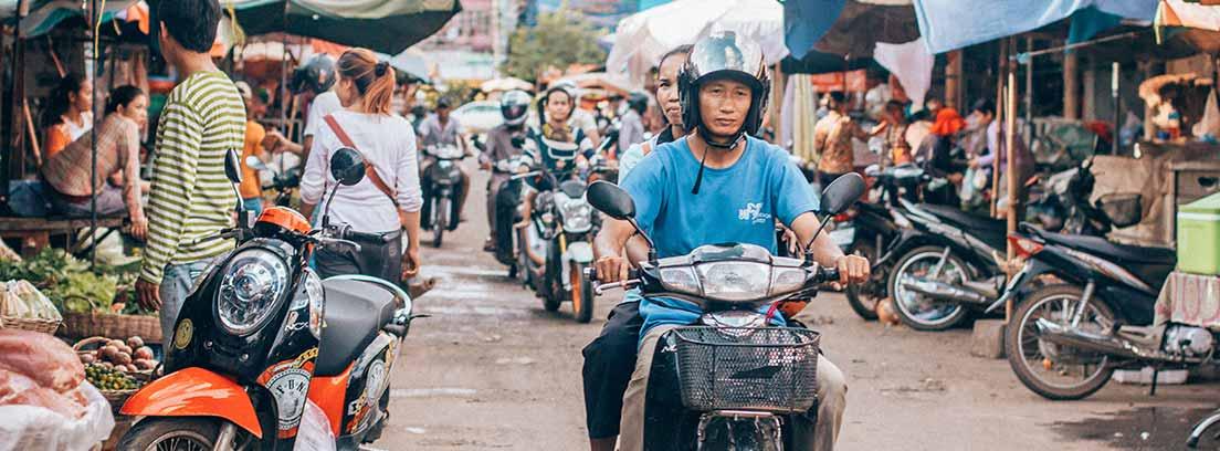 Hombre y mujer montados en moto circulando por mercadillo.