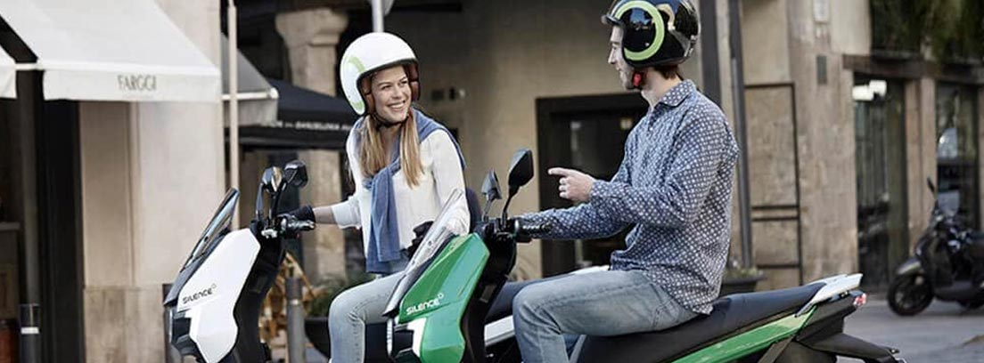 Hombre y mujer con cascos y montados en la Silence S01.