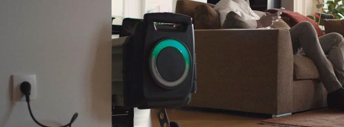 Batería b de una moto SIlence encufada en un enchufe de casa junto a un sillón.