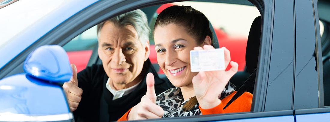 Mujer dentro de un coche mostrando su carné de conducir junto a su profesor de autoescuela