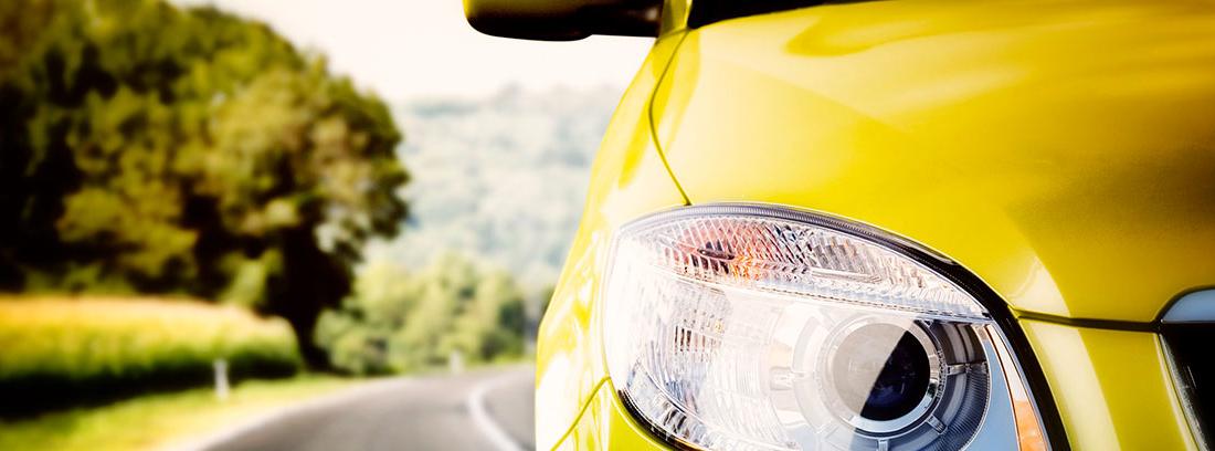 Vista parcial y delantera de faro de coche en carretera
