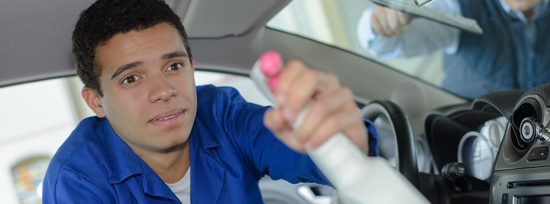 Hombre con pulverizador dentro de coche