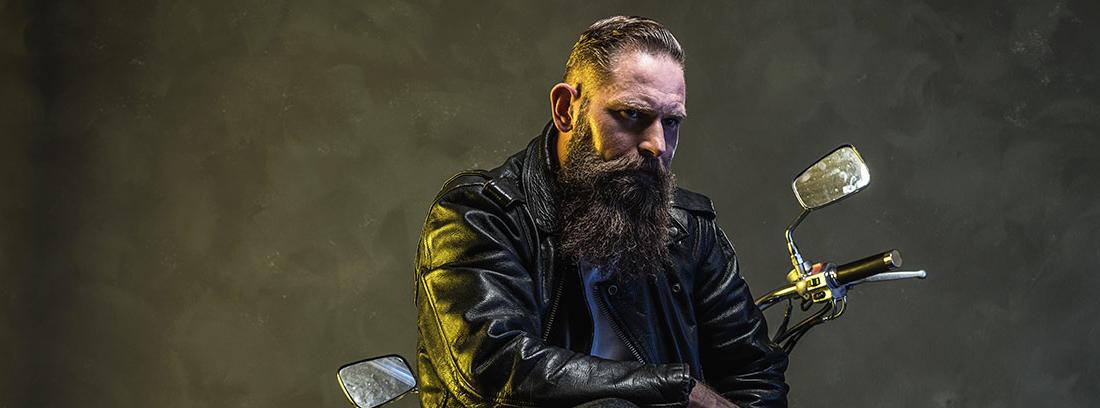 Motero con barba posando con una moto