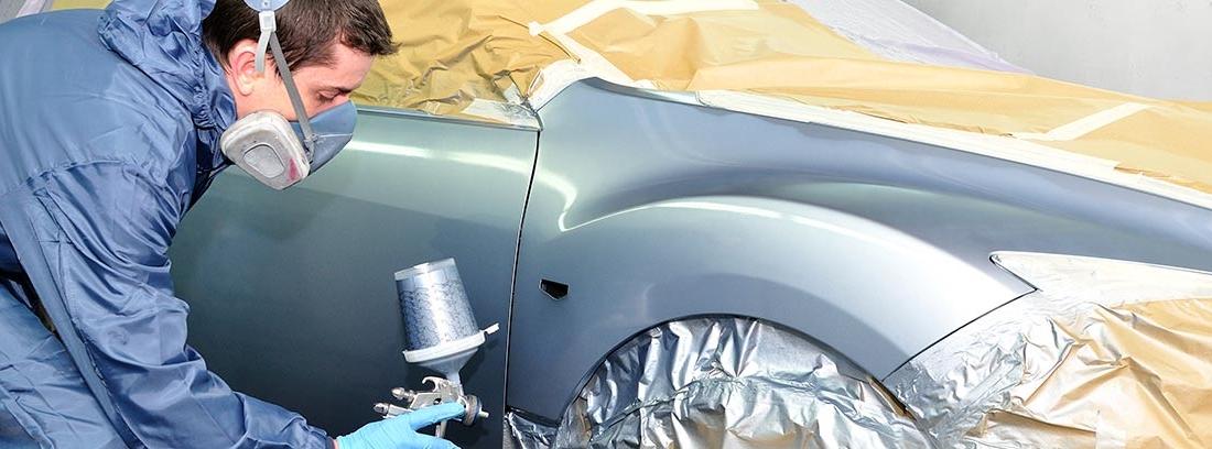 Hombre pintando un coche con una pistola