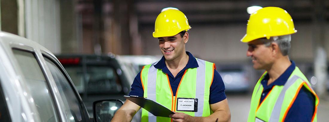 Dos técnicos con casco chaleco amarillo junto a un coche y con carpeta en la mano.