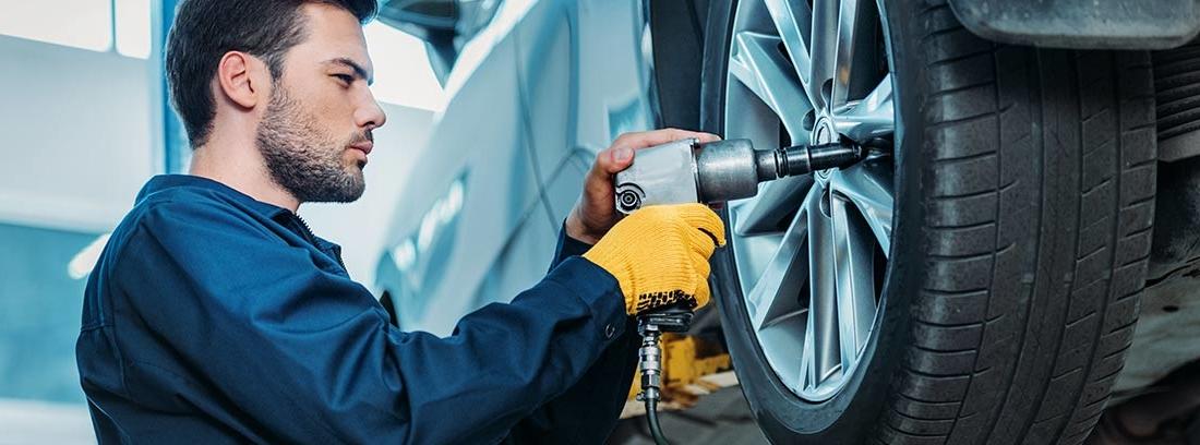 Hombre con mono azul y herramienta sobre rueda de coche elevado en taller.