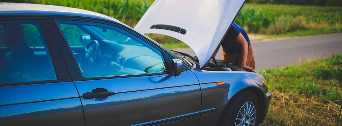 Coche con capó abierto y persona mirando zona motor.
