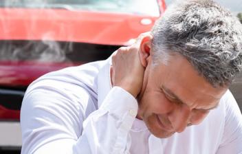 Hombre tocándose el cuello y coche siniestrado a su espalda