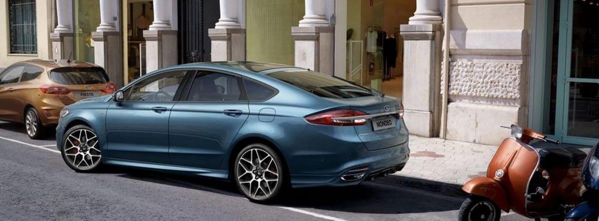 Ford Mondeo de color azul en plena maniobra de aparcamiento en una ciudad