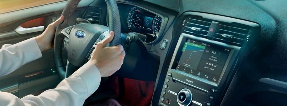 Detalle del volante y la pantalla de infoentretenimiento del Ford Mondeo con vista de los brazos del conductor