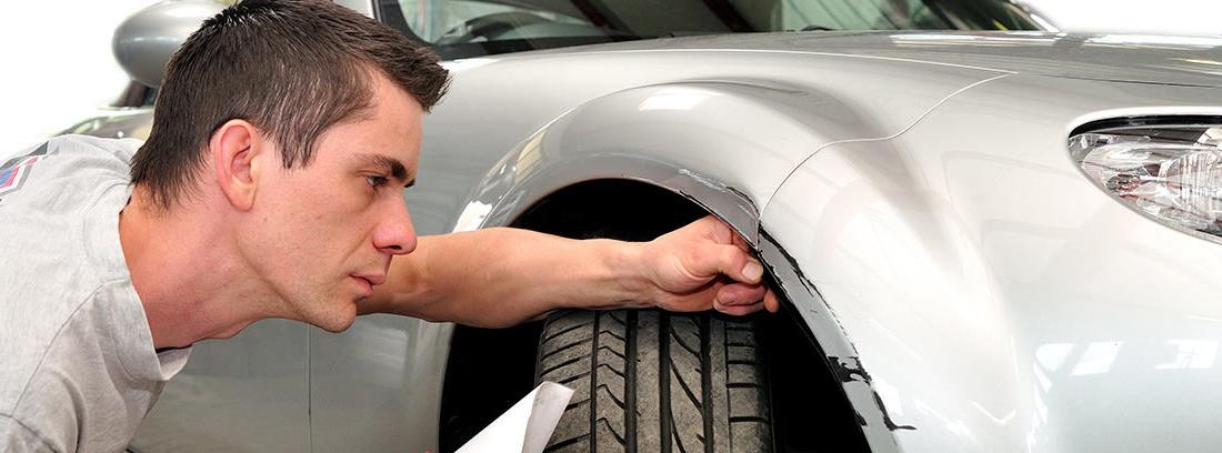 Perito de coche con folios y bolígrafo observa atentamente el guarda barros de un coche.