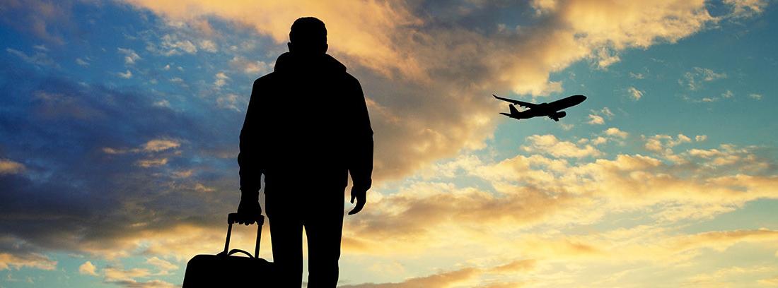 Hombre andando con una maleta y un avión volando en un atardecer