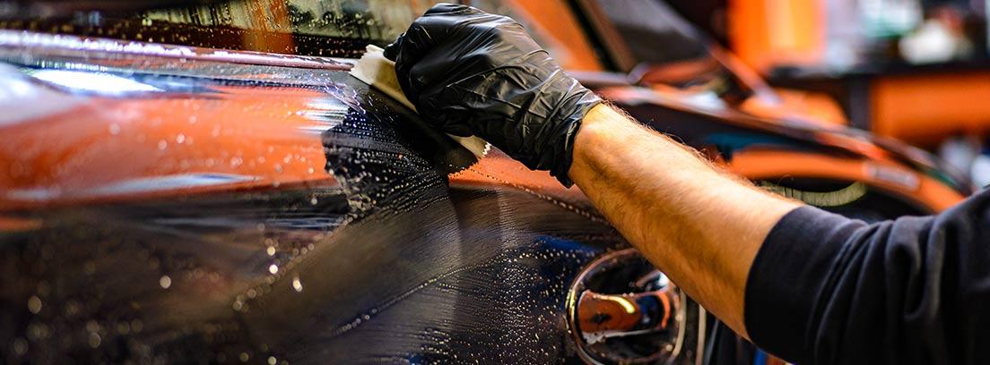 Vista de una mano de hombre limpiando un coche