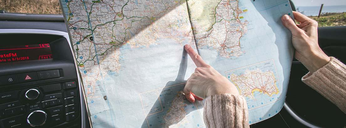 Persona con un dedo puesto en mapa de papel dentro de un coche