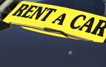 Coche en alquiler con letrero amarillo en que se lee rent a car
