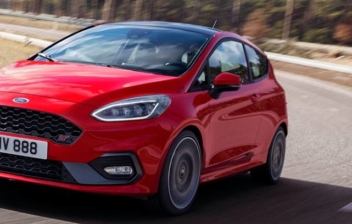 Coche model Ford Fiesta de color rojo circulando por una carretera.
