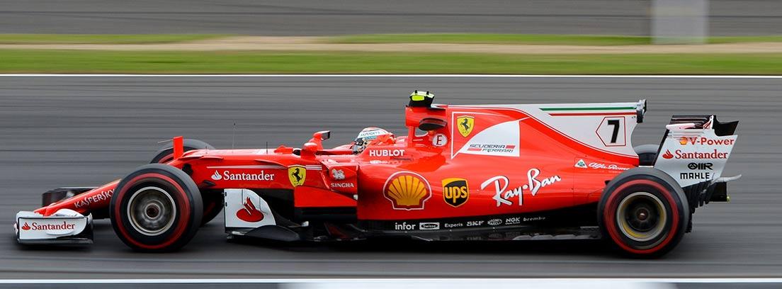 Coche de fórmula 1 rojo rodando por circuito de carreras.