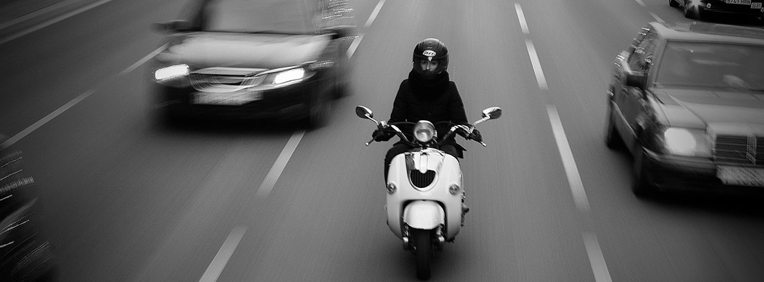 Hombre con casco circulando con su moto por la ciudad