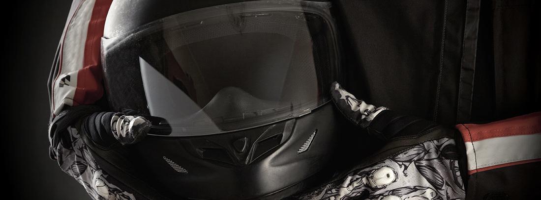 Manos sujetando un casco de moto negro