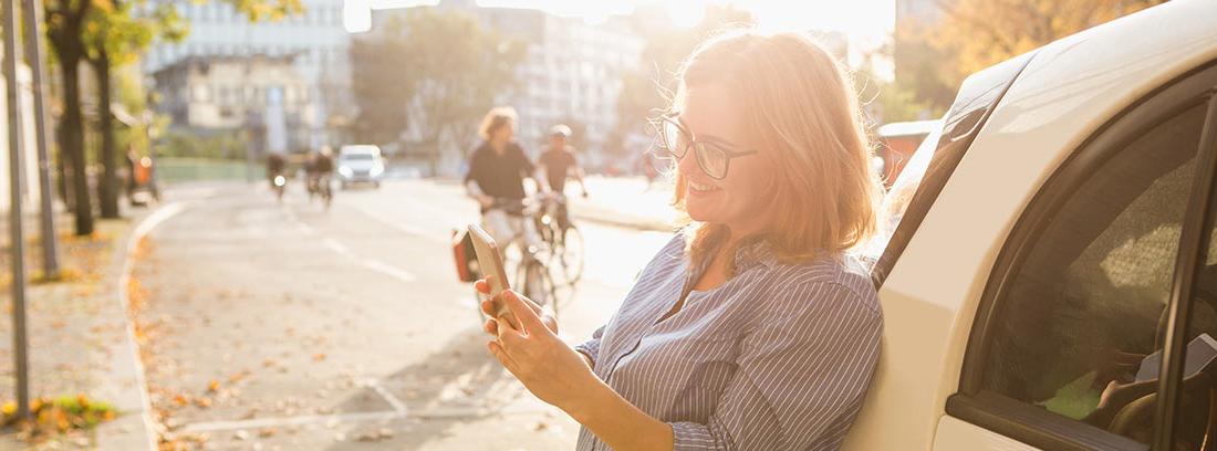 Mujer mirando un móvil sonriente apoyada en un coche eléctrico pequeño