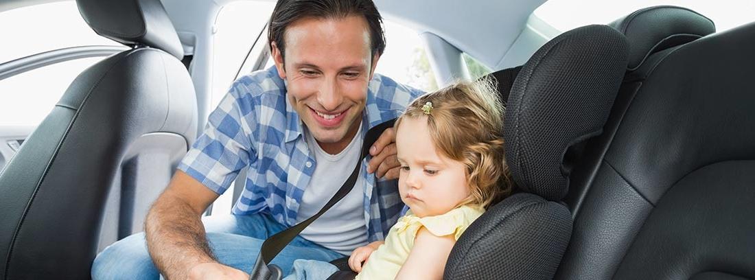 Hombre colocándole el cinturón de seguridad a una niña
