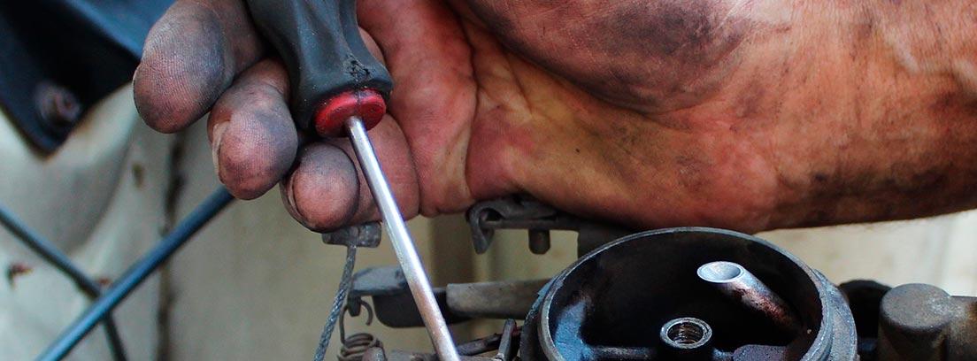 Mano con destornillador reparando un motor