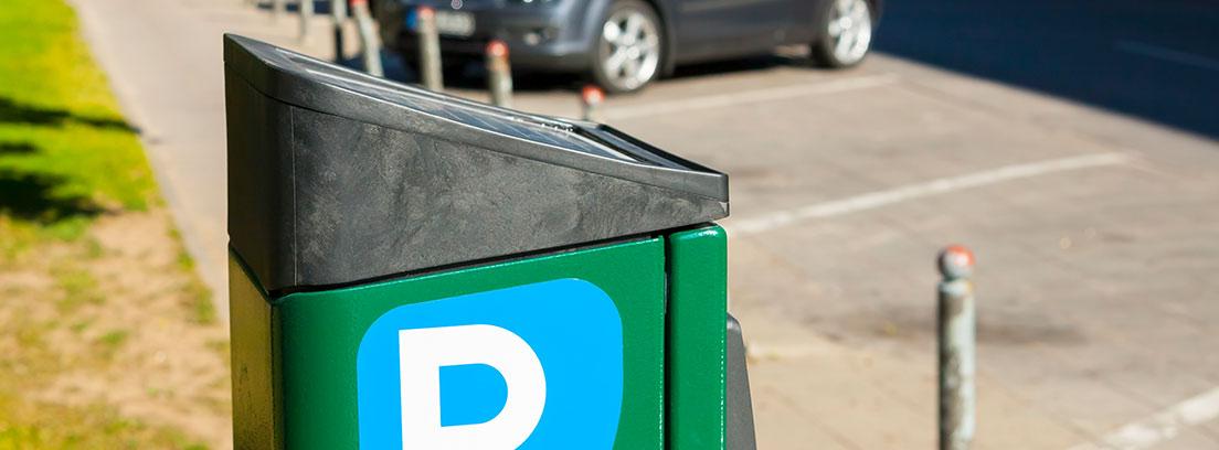 Parquímetro de zona de estacionamiento regulado y coches aparcados