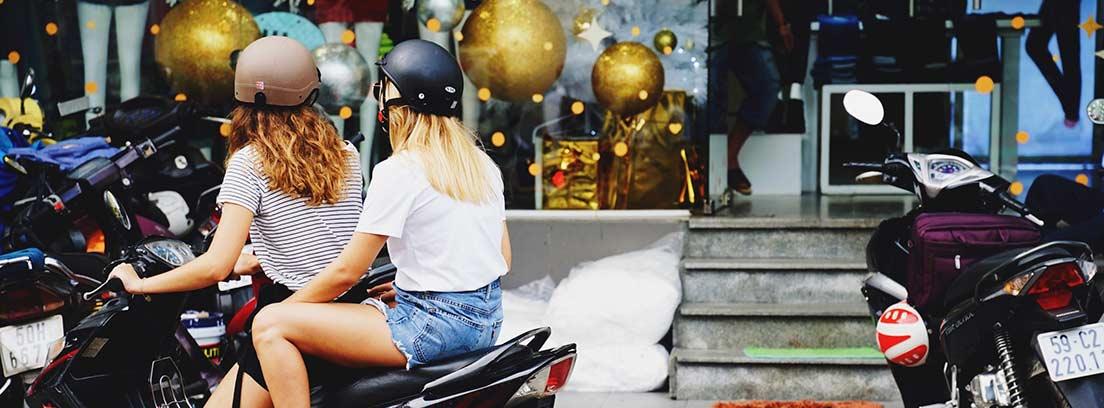 Dos mujeres con casco sobre una motocicleta mirando hacia un escaparate