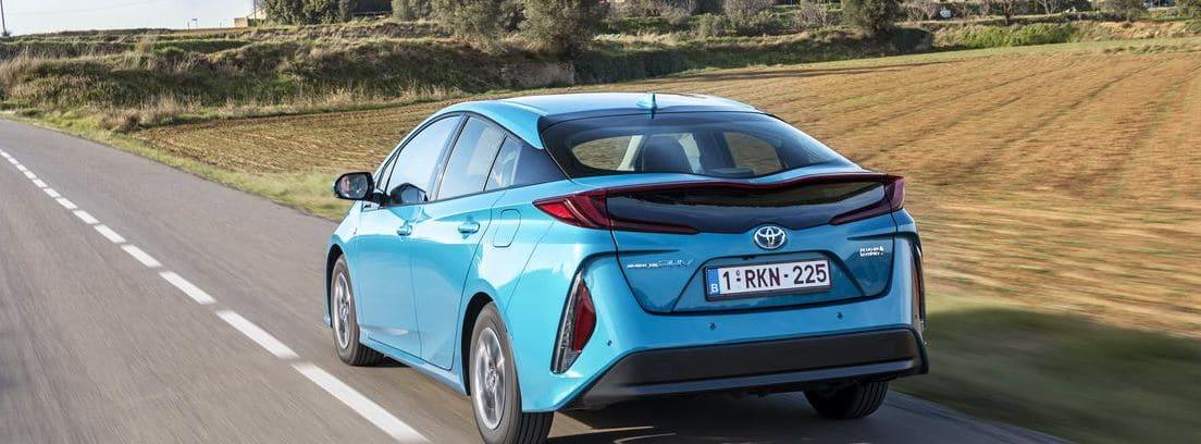Vista trasera del nuevo Toyota Prius Plug-In azul circulando por una carretera