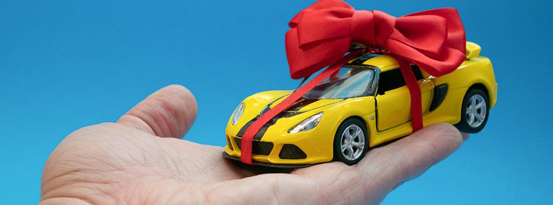 Mano sujetando un coche de juguete con un lazo de regalo