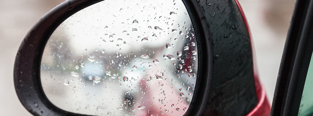 Espejo retrovisor de coche con gotas de lluvia.