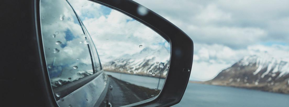 Retrovisor de coche con gotas de lluvia y paisaje nevado